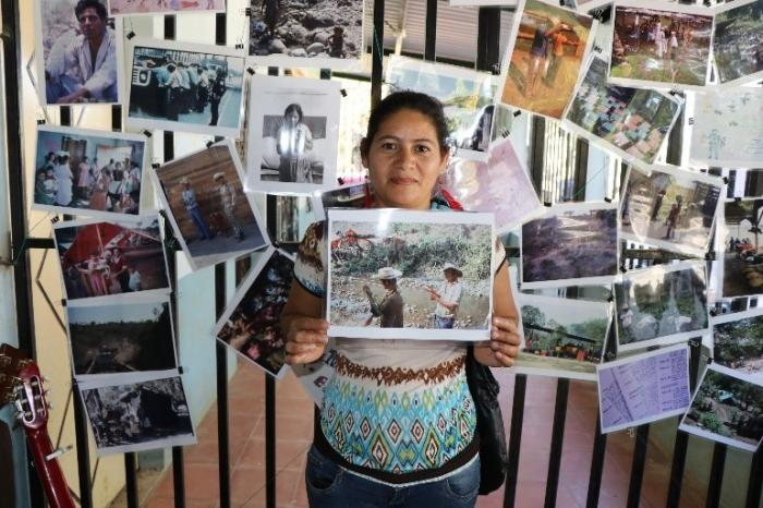 A young woman in Milingo finds a photo of family members working in a refugee camp - photo by Amanda Grzyb