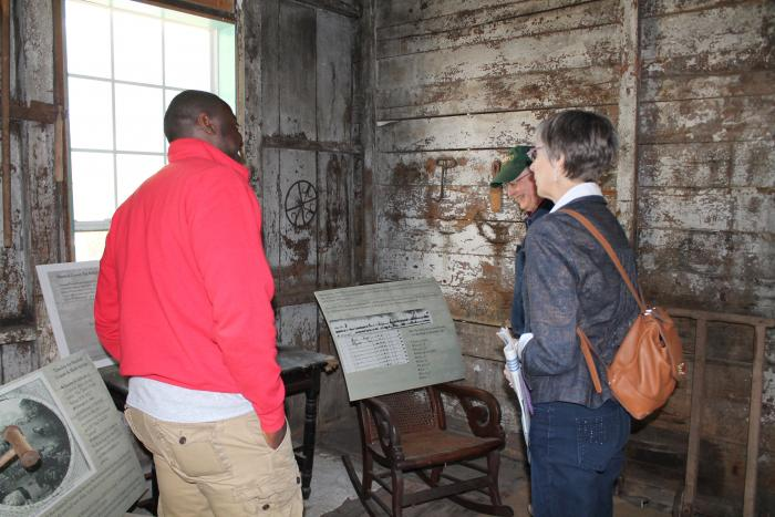 Sociology graduate student Kyle Chandler giving tour to visitors at the Craft House quarters in Holly Springs