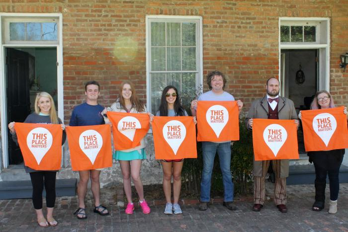 Student visitors and Behind the Big House Program volunteers photographed in front of the Burton Place kitchen/quarters