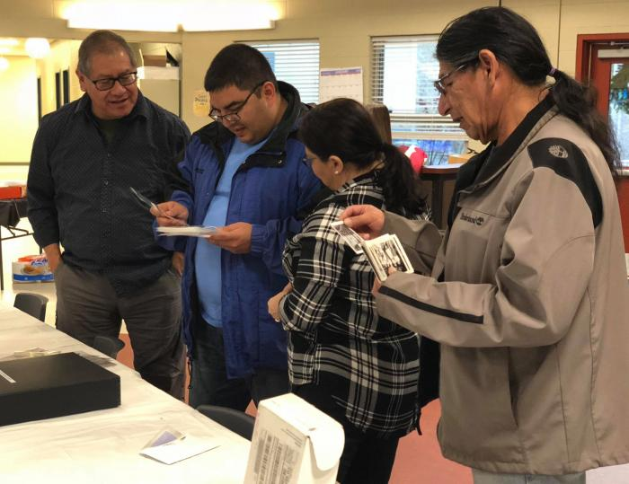 Tuti community members review photos at the kick-off event at the Snowbird Youth Center in January 2018